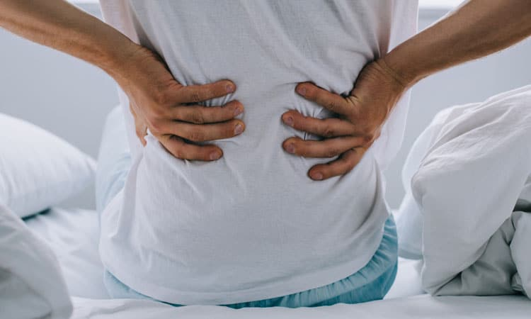 man holding bacl with pain from a herniated disc