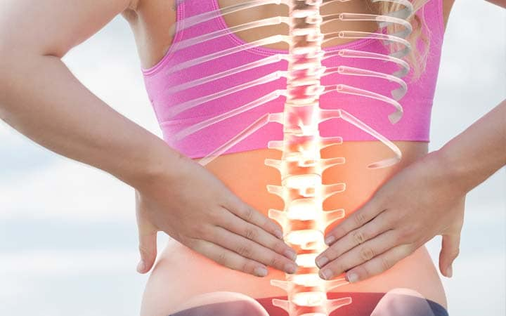 woman holding back needing to have her spine aligned