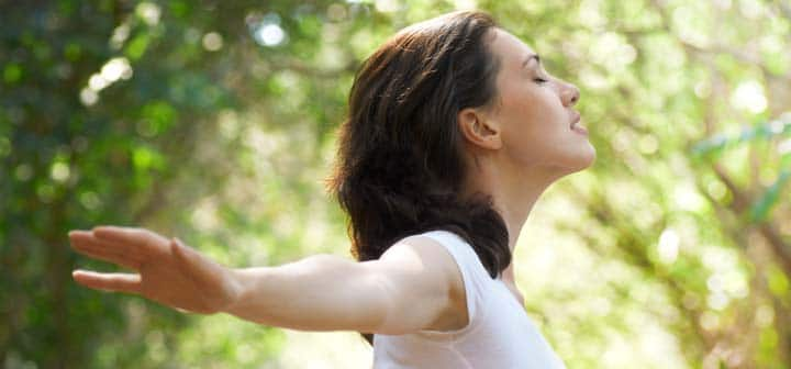 woman with her arms in the air on a sunny day breathing and optimistic